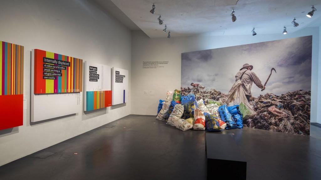 Valkoisessa galleriatilassa on vasemmalla seinällä tauluja, joissa on värikkäitä viivoja ja oikealla edessä kuva kaatopaikalla työskentelevästä miehestä. teoksen edessä on roskasäkkejä.