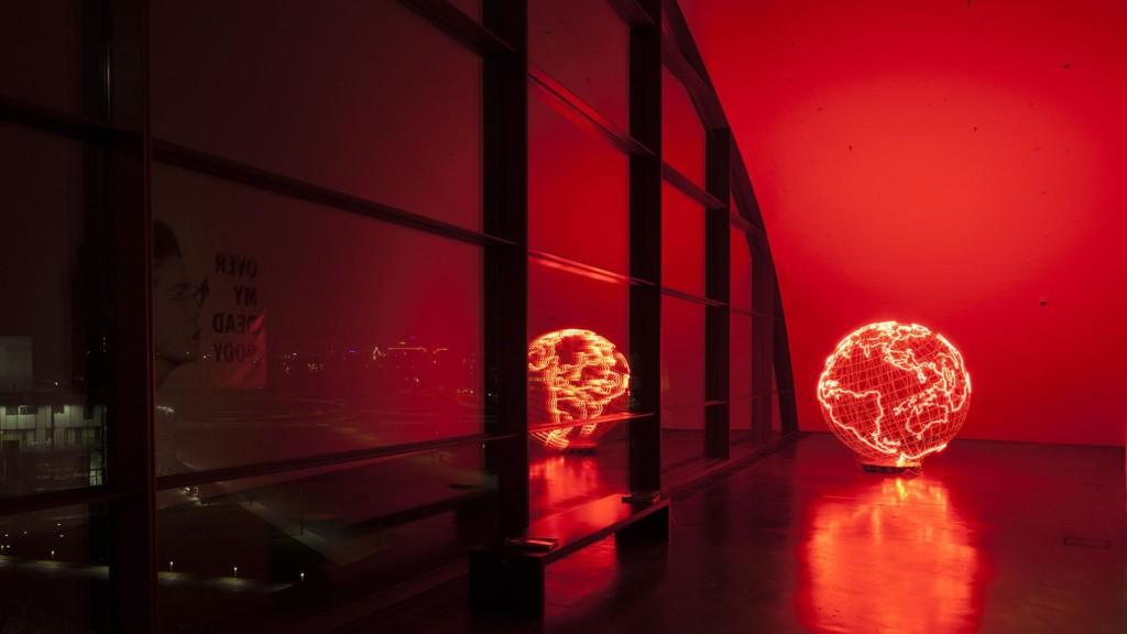 Kiasman viidennen kerroksen päätyikkunan vieressä on maapalloveistos, joka hohtaa punaista neonvaloa.