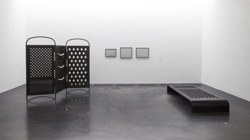 Raastinrautaa muistuttava mustat sermi ja penkki vaaleassa näyttelytilassa. Takaseinällä kolme taulua.