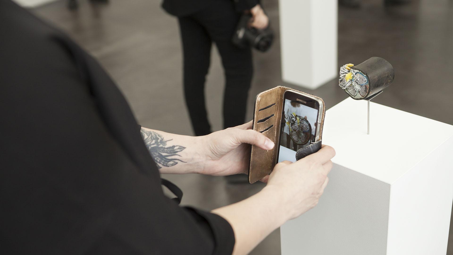 Henkilö ottaa kuvaa kännykällä taideteoksesta.