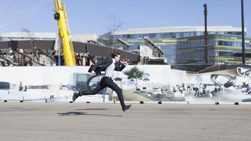 Pukuun pukeutunut mies juoksee kovaa vauhtia työmaa-aidan edustalla.