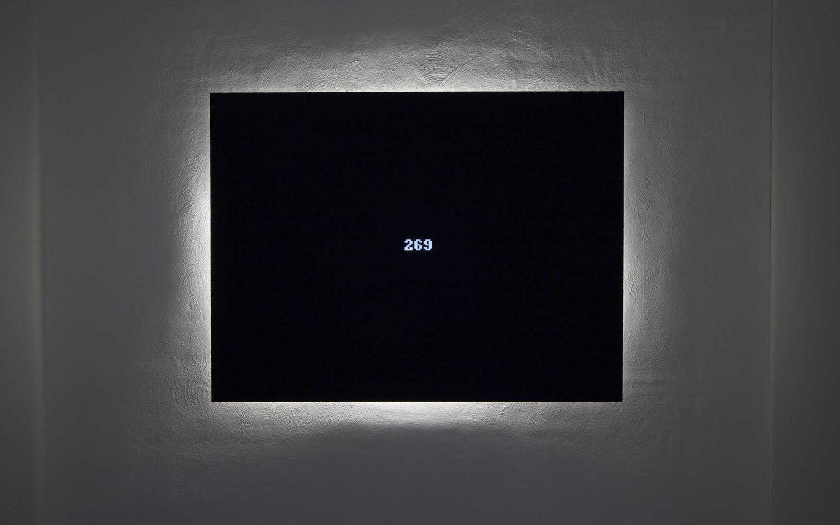 Valkoiselle seinälle on ripustettu musta näyttö, jossa näkyvät numerot 269. Näytön takana on valkoinen valo.