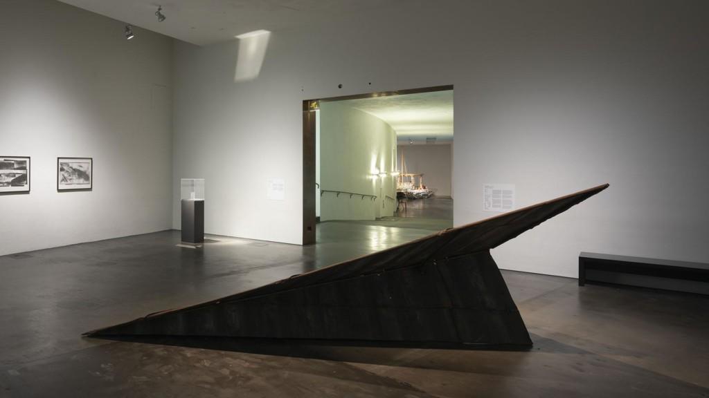 Näkymä galleriatilaan. Etualalla lattialla on viisto metallinen veistos, jonka takaa oviaukosta näkyy seuraavaan galleriatilaan.