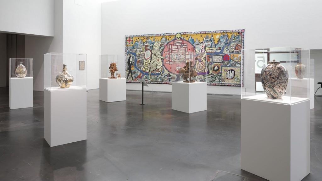 Kuusi ruukkua valkoisilla jalustoilla lasivitriineissä galleriatilassa. Taustalla kirjava seinäkangas.