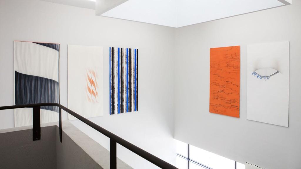 Kurkistus parvekkeelta valkeaan galleriatilaan, jonka seinän yläosaan on kiinnitetty viisi maalausta. Vasemmalla kolme maalausta, joissa on raitoja ja oikealla oranssi maalaus, mustilla aaltokuvioilla, sekä valkoinen maalaus, jossa suljettu silmä.