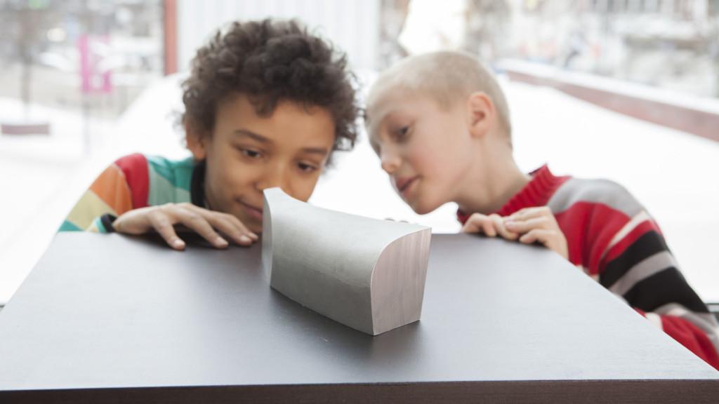 Kaksi poikaa tutkii Kiasma-rakennuksen pienoismallia.