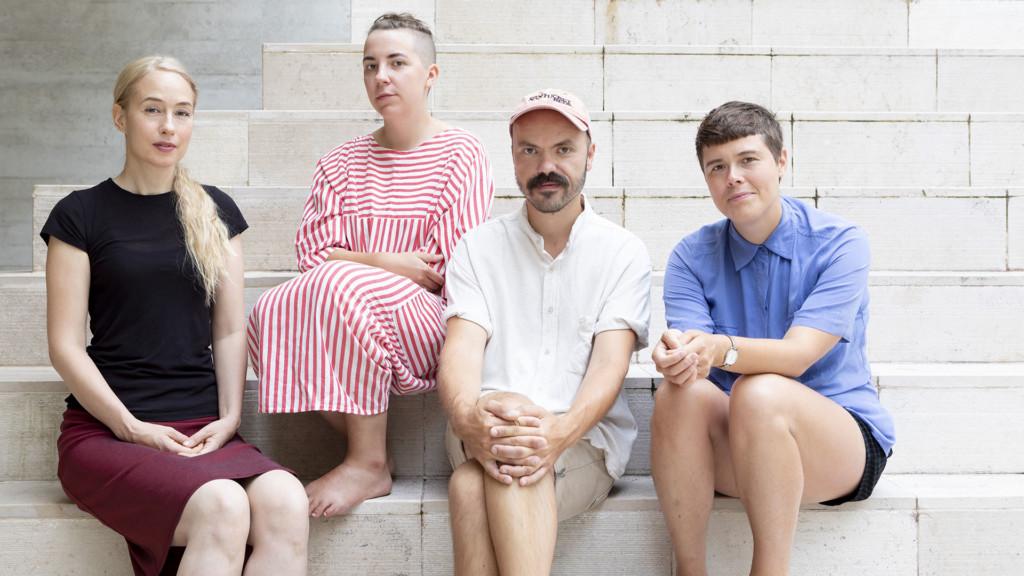 Kolme naista ja mies istuvt portailla kesäisissä vaatteissa.
