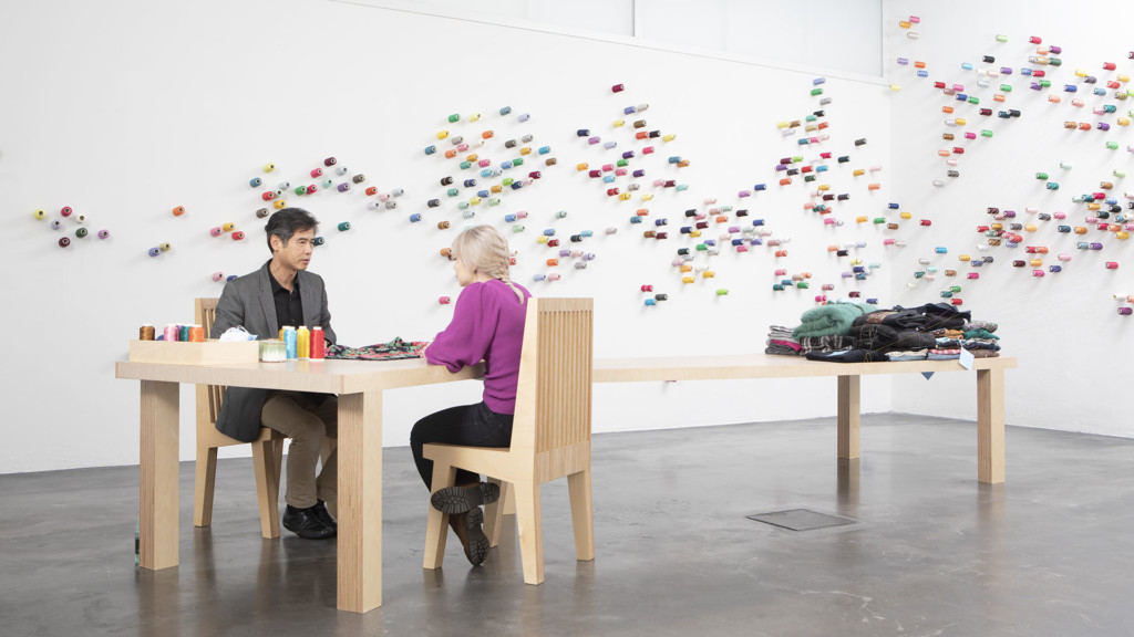 Mies ja nainen juttelevat puunvärisen pöydän äärellä. Valkeaan seinällä pöydän takana on kiinnitetty värikkäitä ompelulankarullia. Pöydän päässä on kasa vaatteita.