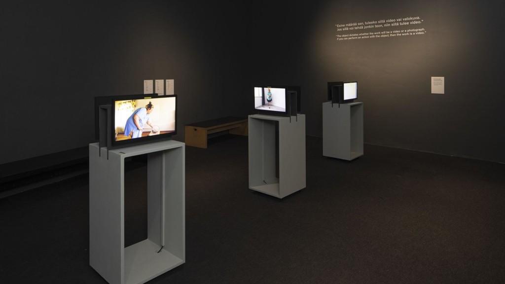 Kolme näyttöä valkoisilla jalustoilla tummaseinäisessä näyttelytilassa.