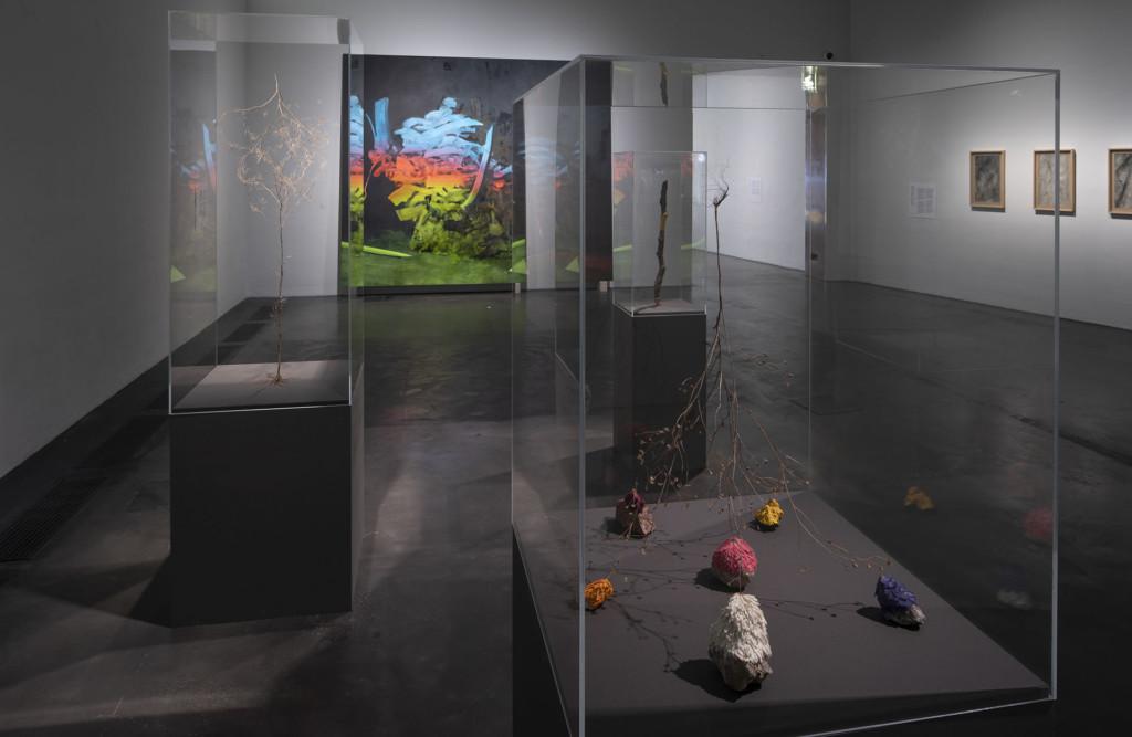 Kolme lasivitriiniä näytelytilassa, joissa veistoksia. Taustalla värikäs maalaus.