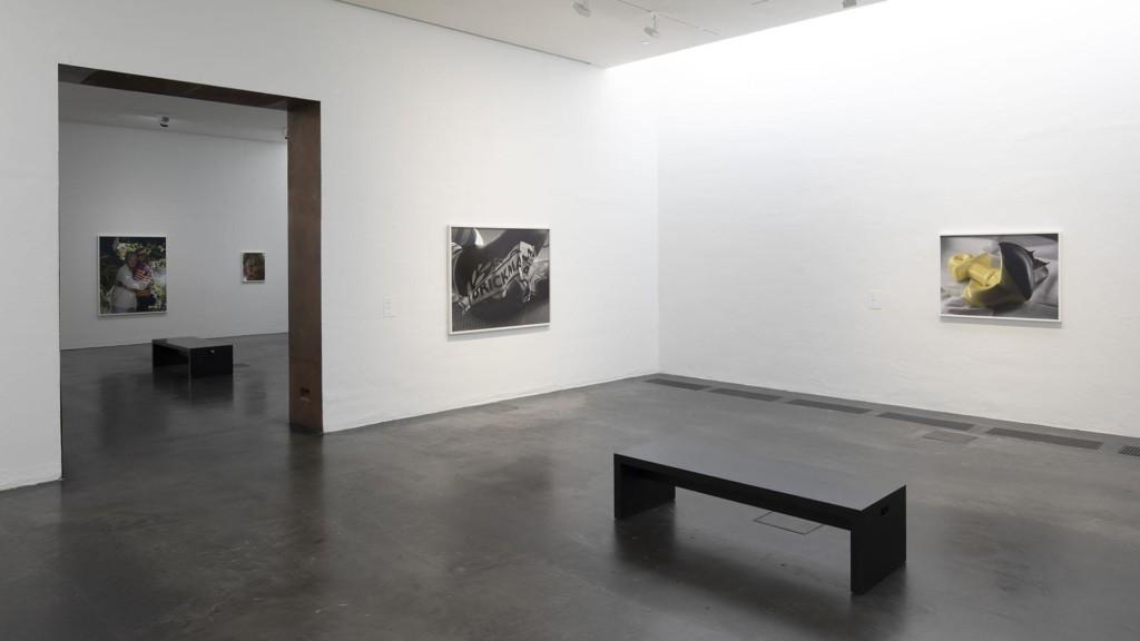 Kaksi valokuvateosta valkoisen näyttelytilan seinillä, sekä musta penkki. Vasemmalla olevasta oviaukosta näkyy toiseen näyttelytilaan, jossa kaksi valokuvateosta ja musta penkki.