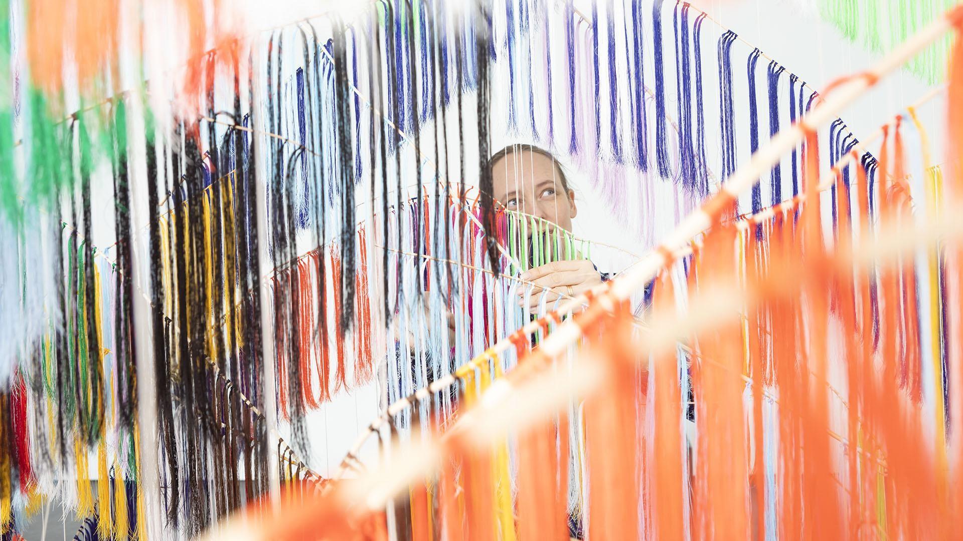 Taiteilija Outi Pieski teoksensa Our Land, Our Running Colours takana.