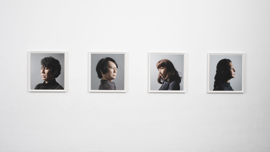 Neljä muotokuvaa vaalealla seinällä. Valokuvia.