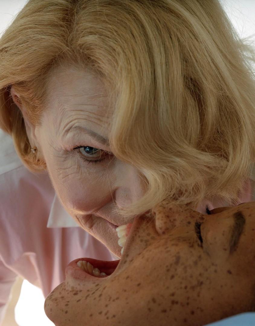 Vanha nainen tuijottaa kameraan, edessä makuulla nuori nainen kiljuu.