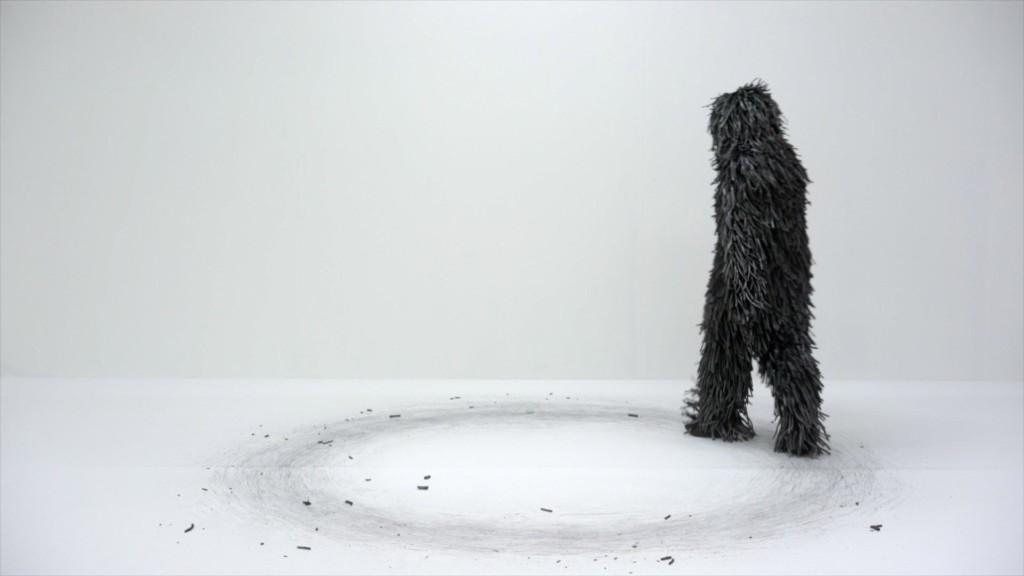 Hiileen pukeutunut hahmo kiertää ympyrää valkealla lattialla. Maahan on piirtynyt ympyrä hiilestä.