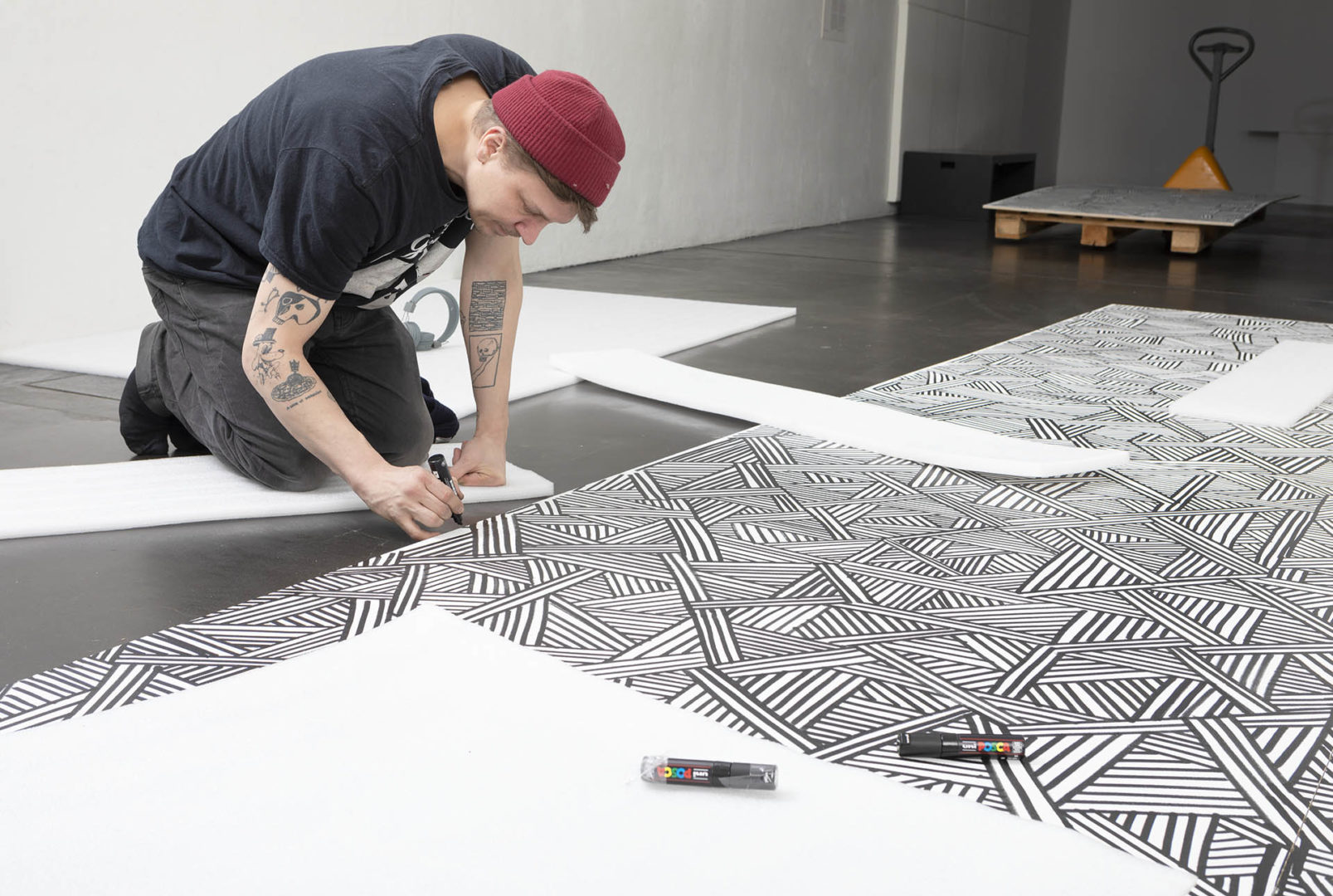 Mies piirtämässä polvillaan.