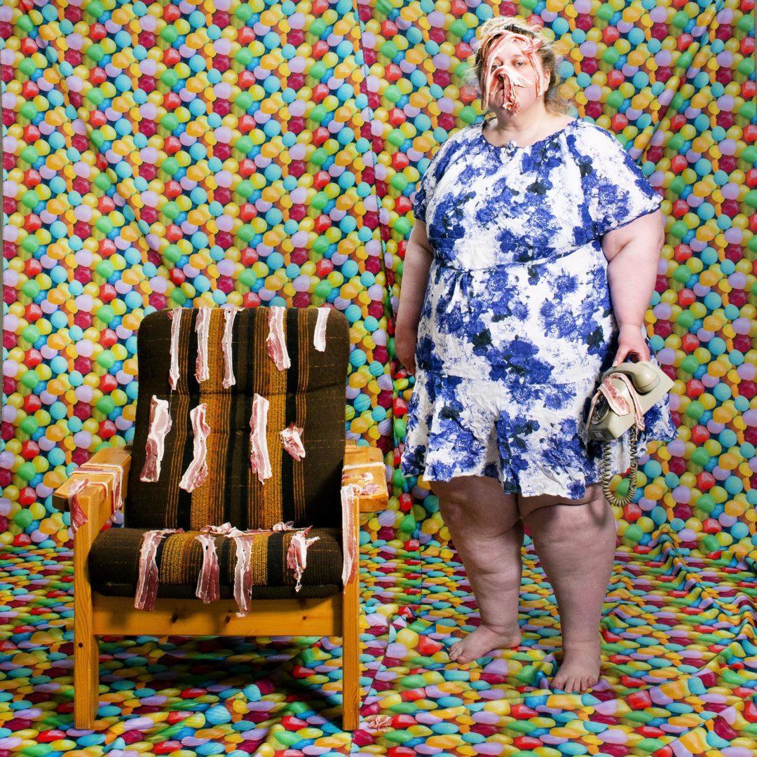 Taiteilija Iiu Susiraja seisoo pekonilla täytetyssä huoneessa tuolin vieressä.