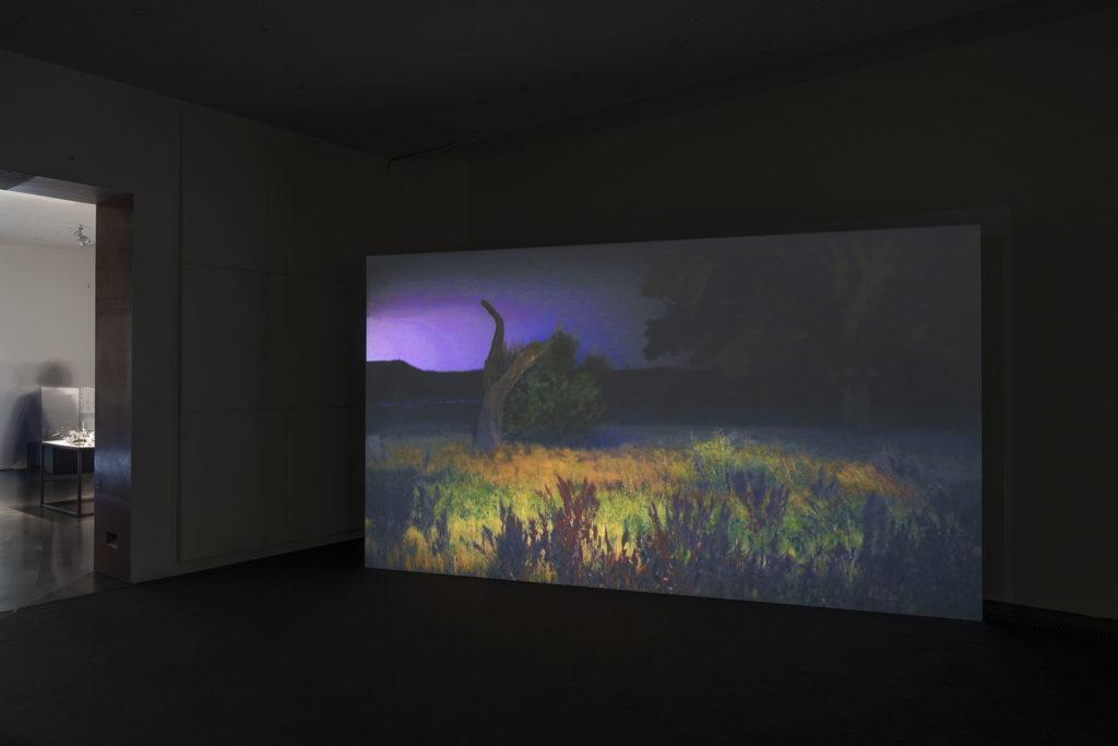 Liisa Lounilan videoteos Kiasman näyttelysalissa. Videolla on kuvattuna villiintynyt puutarha iltahämärässä.