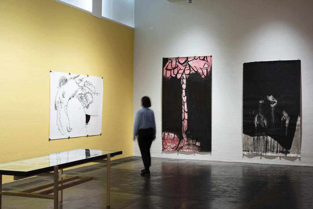 Nainen seisoo Kiasman näyttelysalissa ja katsoo tauluja.