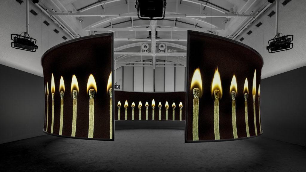 Ripustuskuva taiteilija Doug Aitkenin videoteoksesta, jossa ympyränmuotoisella näytöllä palaa tulitikkuja.