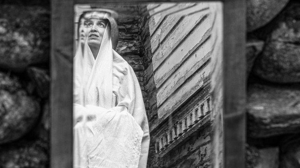 Peilikautta kuvatussa kuvassa valkoiseen kaapuun puettu nainen katsoo yläilmoihin vanhan talon edessä.