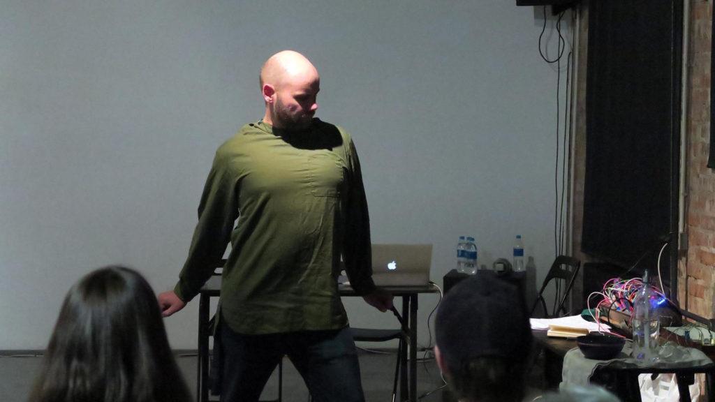 Esiintyjä vihreässä paidassa kahden katsojan edessä.