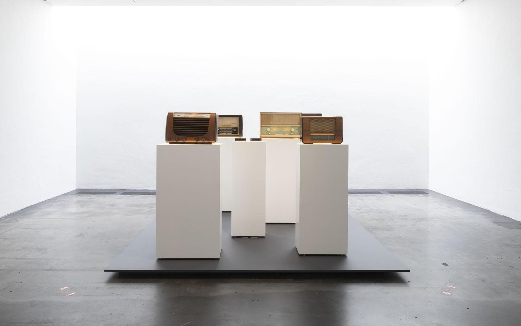 Vanhoja putkiradioita valkoisten pylväiden päässä näyttelysalissa.