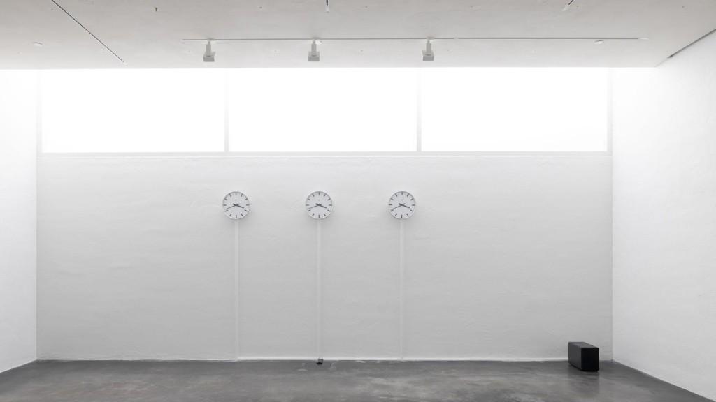 Kolme valkoista seinäkelloa valkoisella seinällä.