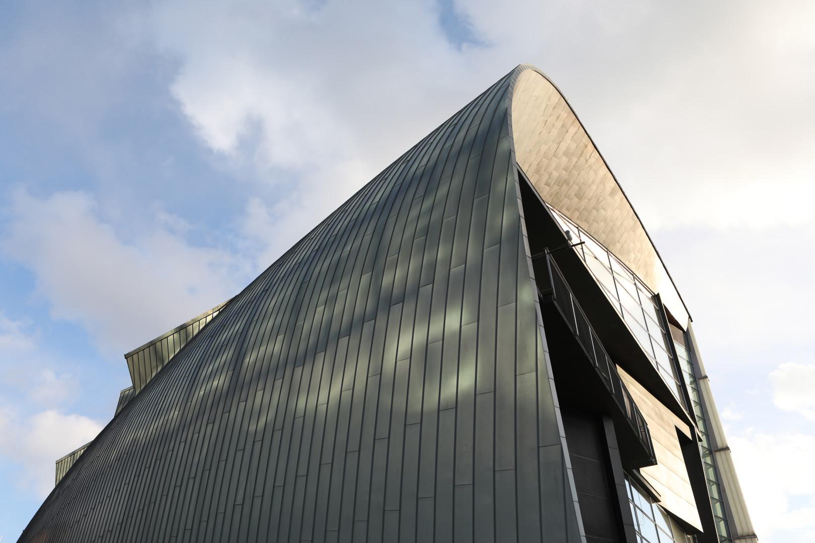 Kiasma-rakennuksen katto ja seinää vasten puolipilvistä taivasta.