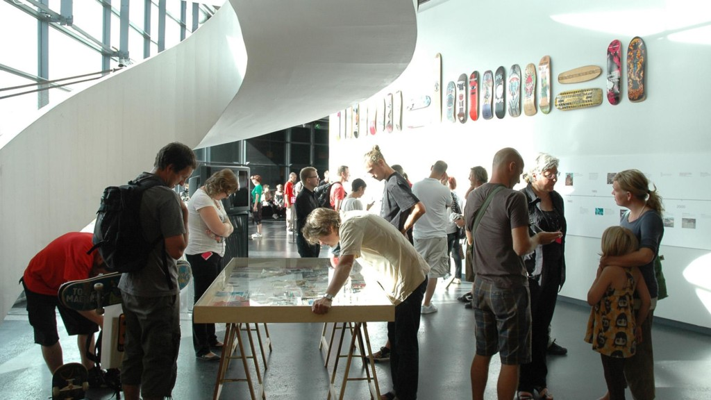 Ihmisiä katsomassa rullalautanäyttelyä.