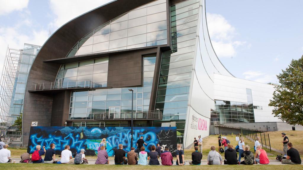 Graffitiseinä ja ihmisiä Kiasman edustalla.