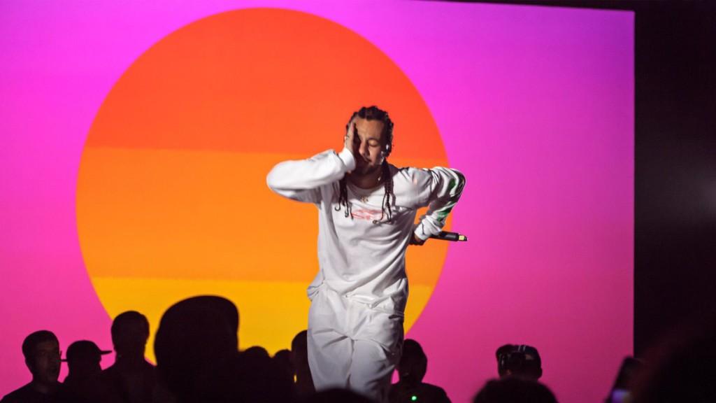 Räppäri lavalla pinkki-oranssia taustaa vasten.