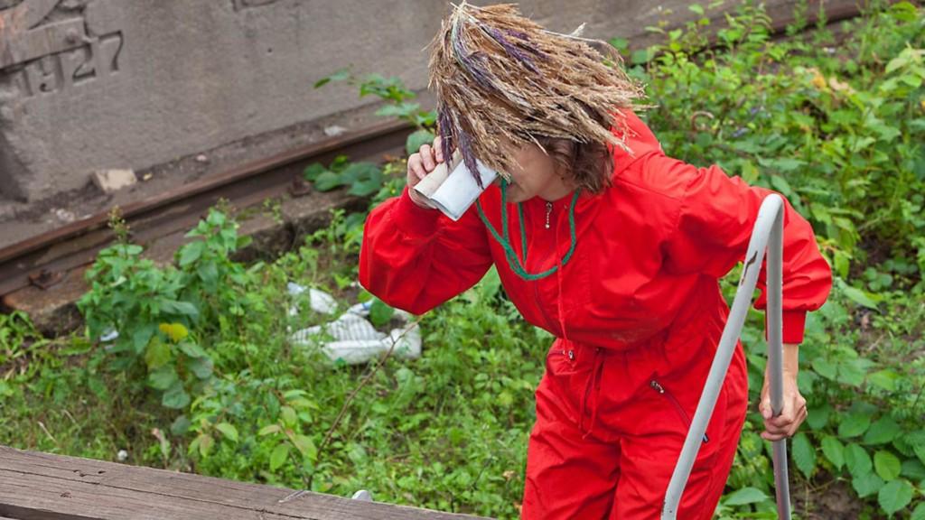 Punapukuinen hahmo katsoo pahvikiikareilla kasveja.