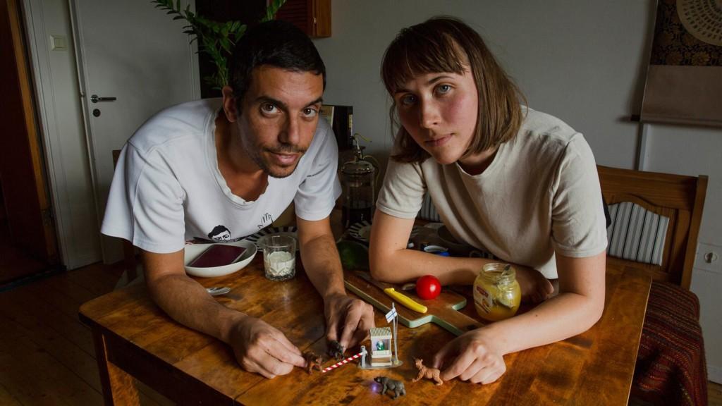 Mies ja nainen pöydän ääressä edessään miniatyyrihahmoja.