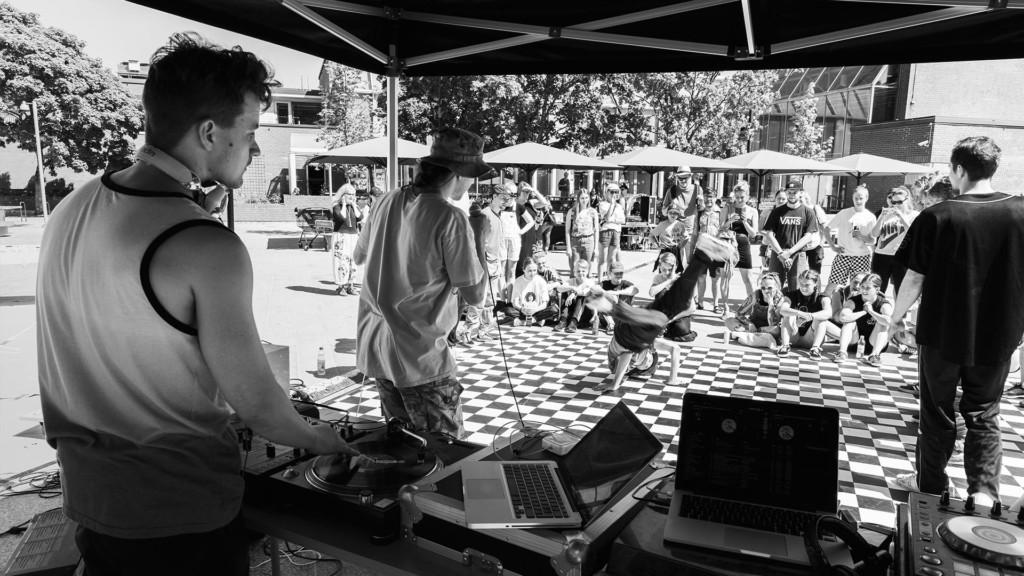 Ulkoilmatapahtuma, jossa DJ soittaa ja tanssitaan breakdancea.