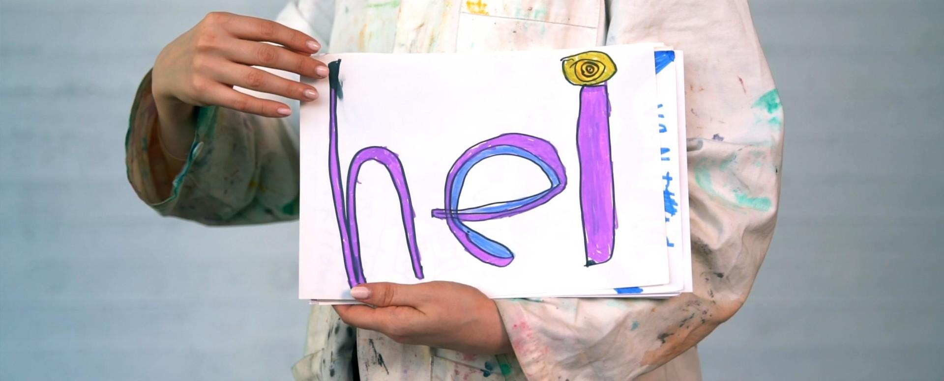 """Koululaisen kirjoittama sana """"hei"""" valkoisella paperilla on osa Tokaluokkalaisten taideretken työpajoja."""