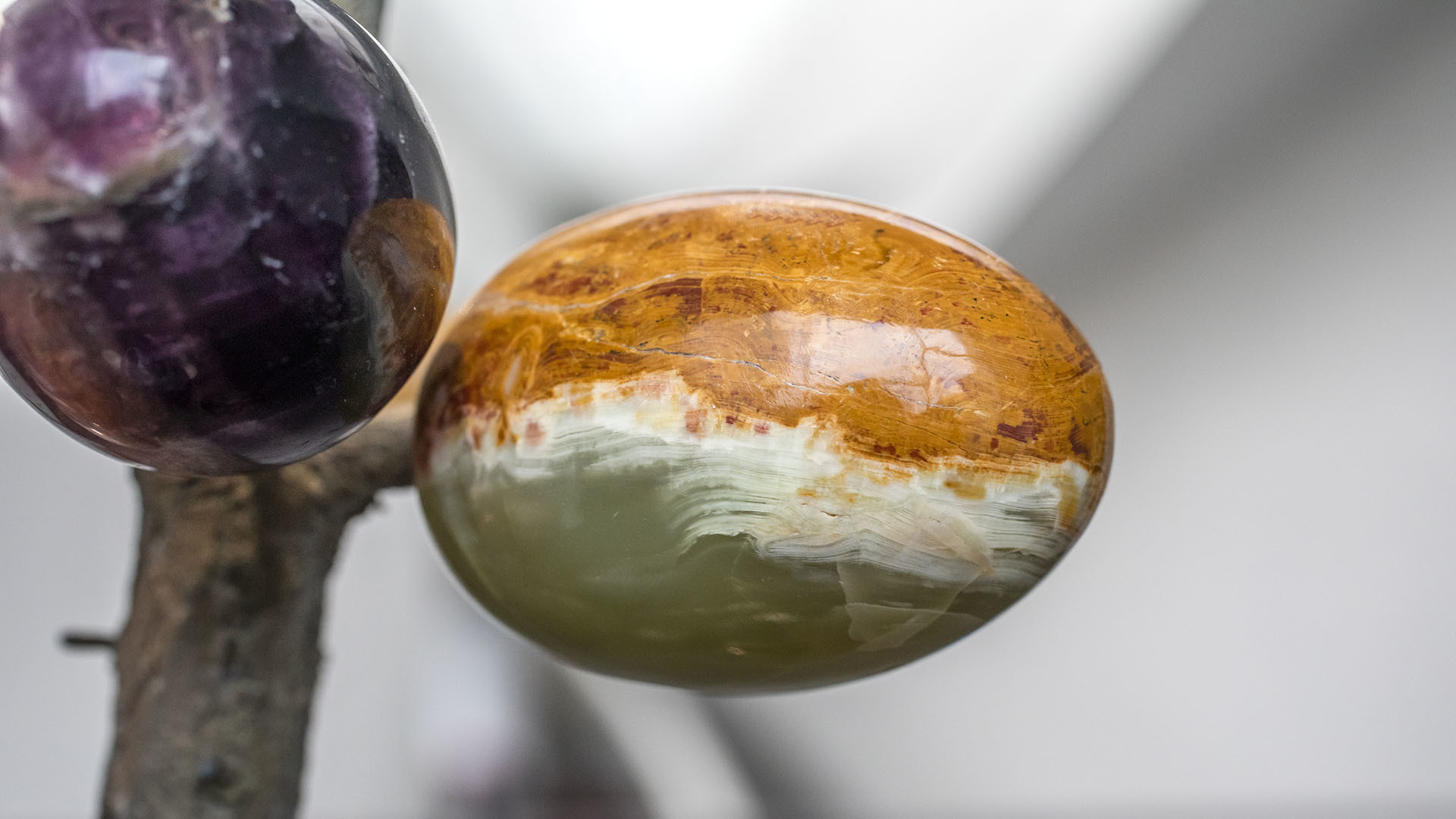 Kananmunan muotoinen kivi, joka on kiinni oksassa.