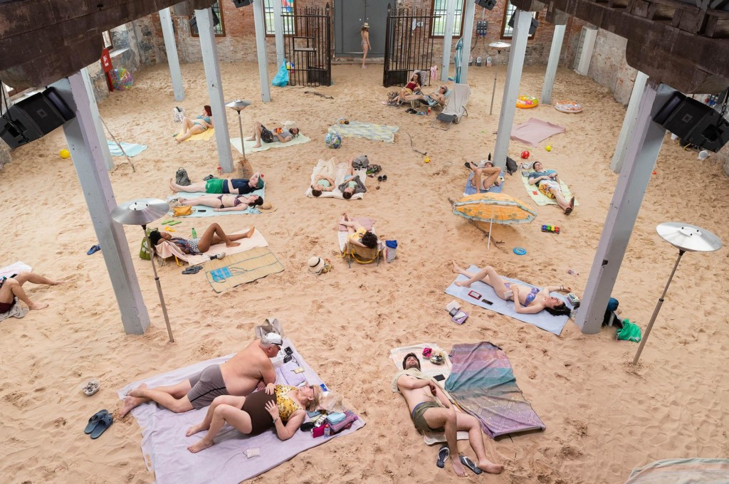 Ihmisiä makaamassa sisätiloihin toteutetulla hiekkarannalla.