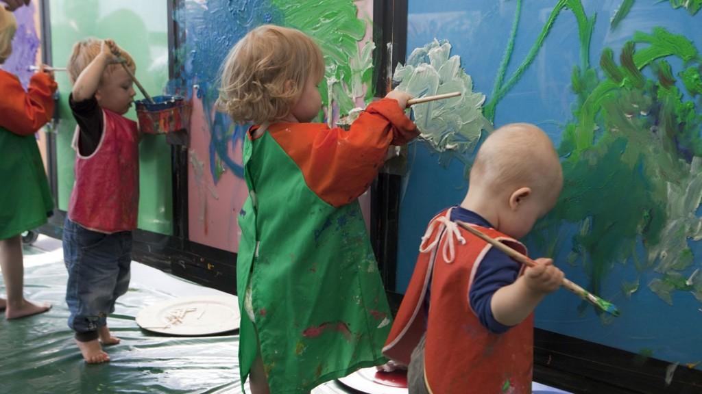 Kolme lasta maalaa pensseleillä seinää.